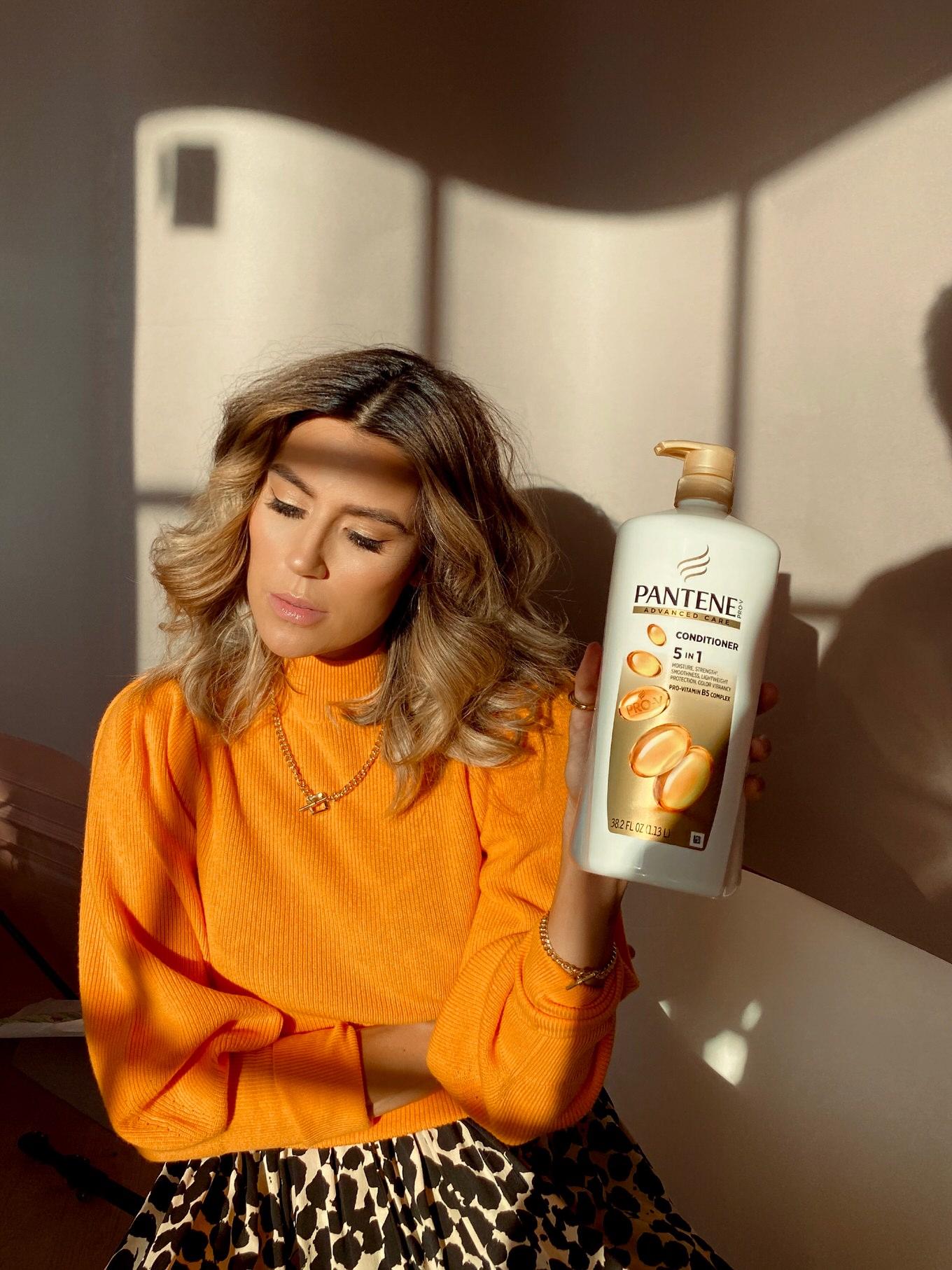christine andrew in orange sweater holding pantene bottle